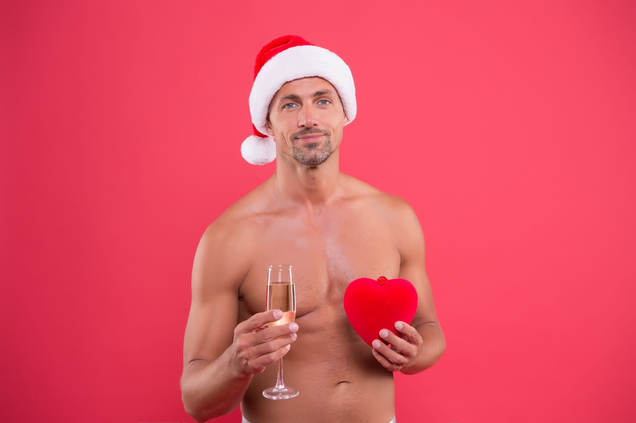 Naughty Santa gives an erotic gift man naked in Santa hat with champagne